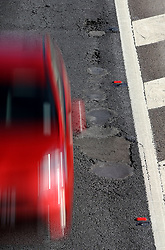File photo dated 20/03/18 of a car passing potholes on the M20 near Ashford in Kent. More than £200 million will be allocated to English councils to improve road surfaces, the Department for Transport (DfT) has announced.