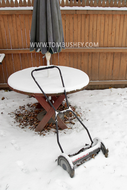 Middletown, NY - Snow covers a picnic table and a rotary lawn mower in the backyard of a suburban house after a winter storm on Dec. 2, 2007.