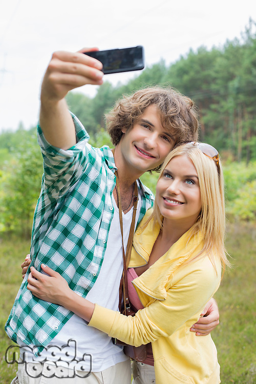 Happy young couple taking self portrait through cell phone in field