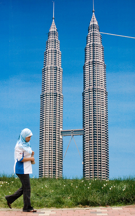Malaysian woman walks past advertisement board showing Petronas Twin towers