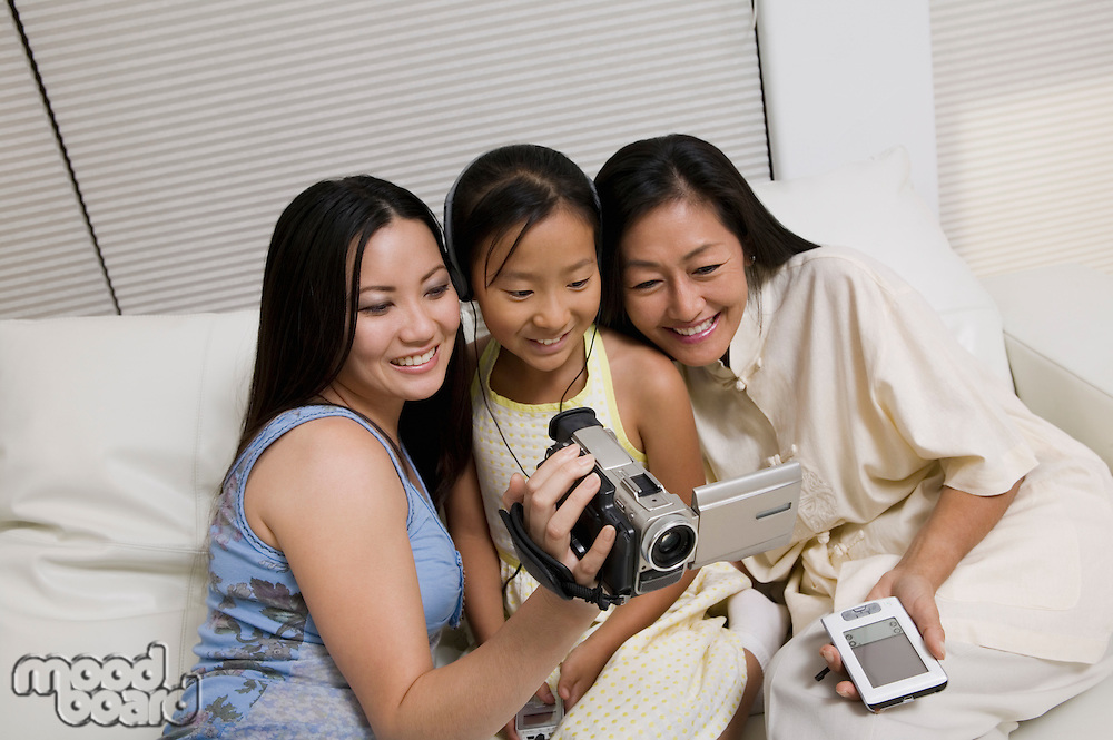 Mother and Daughters with Video Camera and PDA