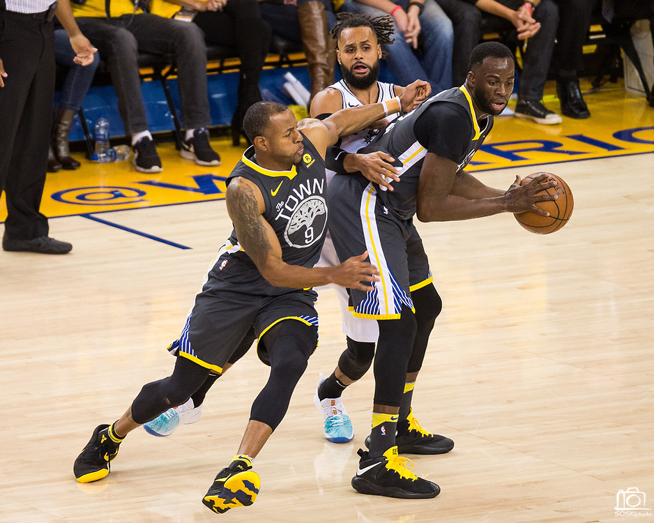 Golden State Warriors forward Draymond Green (23) hands the ball off to Golden State Warriors forward Andre Iguodala (9) against the San Antonio Spurs during Game 2 of the Western Conference Quarterfinals at Oracle Arena in Oakland, Calif., on April 16, 2018. (Stan Olszewski/Special to S.F. Examiner)