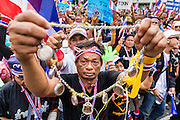 26 NOVEMBER 2013 - BANGKOK, THAILAND:  A Thai anti-government protestor holds up his religious amulets during a rally at the Ministry of Finance in Bangkok. Protestors opposed to the government of Thai Prime Minister Yingluck Shinawatra spread out through Bangkok this week. Protestors have taken over the Ministry of Finance, Ministry of Sports and Tourism, Ministry of the Interior and other smaller ministries. The protestors are demanding the Prime Minister resign, the Prime Minister said she will not step down. This is the worst political turmoil in Thailand since 2010 when 90 civilians were killed in an army crackdown against Red Shirt protestors. The Pheu Thai party, supported by the Red Shirts, won the 2011 election and now govern. The protestors demanding the Prime Minister step down are related to the Yellow Shirt protestors that closed airports in Thailand in 2008.    PHOTO BY JACK KURTZ