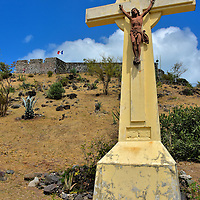 Crucifix at Base of Fort Marigot Hill in Marigot, Saint-Martin<br /> Fort Marigot is located on a hill overlooking the Bay of Marigot. The citadel was built during the 18th century to protect the town&rsquo;s warehouses from British raids. Most people call it by the original name: Fort Louis. Thanks to renovation efforts, it is in much better condition than most of the island&rsquo;s fortresses so it is worth a visit. On a clear day, the elevated view is magnificent. But it takes a while to walk up the road. When you are catching your breath along the way, you can admire this crucifix.