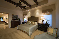 Silk bed cover on double bed in Palm Spring bedroom with beamed ceiling