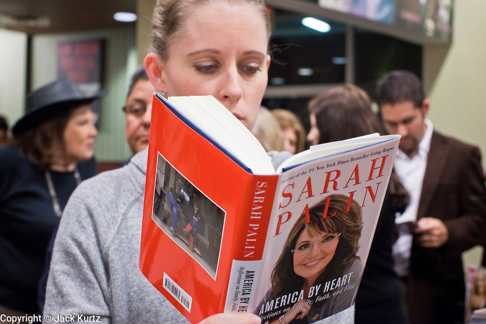 "23 NOVEMBER 2010 - PHOENIX, AZ:  MICHELLE WINTLE, from Mesa, AZ, reads Sarah Palin's new book, ""America by Heart"" while waiting to get the book signed at a Barnes and Noble in Phoenix Tuesday. Palin signed copies of her new book, ""America by Heart"" at the store in north Phoenix Tuesday night, Nov. 23. It was the kick off of her book tour to support America by Heart. Palin is frequently mentioned as a possible Republican candidate for US President in 2012.   Photo by Jack Kurtz"