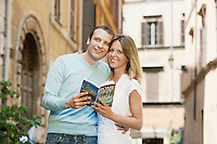 Couple on street in Rome Italy holding guidebook front view