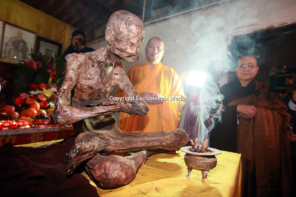 QUANZHOU, CHINA - JANUARY 10: (CHINA OUT) <br /> <br /> Monks stand by monk Fuhou\'s body which was found not rotted after putting in a vat for three and a half years at Puzhao temple on Zimao Mountain on January 10, 2016 in Quanzhou, Fujian Province of China. 94-year-old monk Fuhou died in 2012 and his body was put by the sitting position into a vat with a cover for three and a half years. Monks found that Fuhou\'s body wasn\'t rotted on an opening vat rite on January 10 at Puzhao temple on Zimao Mountain in Quanzhou. The body would be cleaned and stuck with gold to be made into a golden Buddha.<br /> &copy;Exclusivepix Media