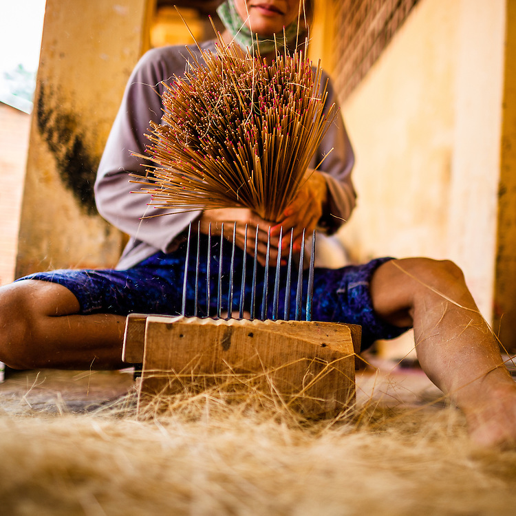 A woman makes incense sticks for use in a nearby pagoda. Tay Ninh, Vietnam