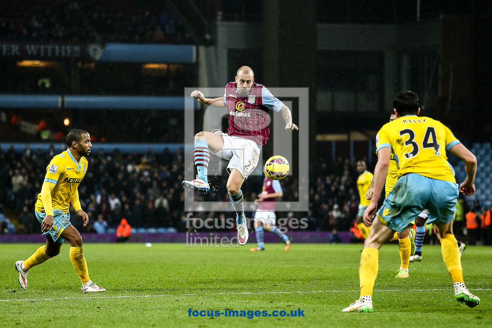 Alan Hutton of Aston Villa (centre)  gets a shot away at goal during the Barclays Premier League match at Villa Park, Birmingham<br /> Picture by Andy Kearns/Focus Images Ltd 0781 864 4264<br /> 01/01/2015