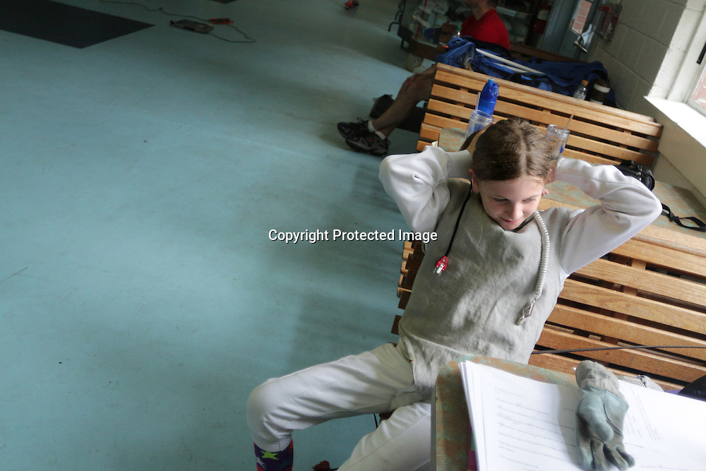 Reaghan Juelke, 11, fixes her hair in between matches during a Cape Fear Fencing Association youth fencing tournament at Tileston Gym in Wilmington, N.C. Saturday May 31, 2014. (Jason A. Frizzelle)