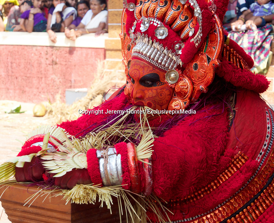A ROAD-SWEEPER YESTERDAY, A GOD TODAY<br /> <br /> A 19th century Indian missionary once said: There are certain places that are rarely seen; and in those you will find a special sort of magic<br /> <br /> Theyyam is one of those magical celebrations that takes place annually in South India.<br /> <br /> It's a religious dance-drama that takes place in just two districts of Kerala; in Kannur and Kasargod, and is celebrated during the months of December - February. Believed to pre-date Hinduism, Theyyam is said to be a corrupted form of the word Deivam meaning God and Aattam meaning Dance. The meaning of Theyyam thus becomes Dance of the Gods.  <br /> <br /> It's a ritual art form at least 1,500 years old combining both religious and spiritual traditions; and Theyyam appear in more than 450 forms.<br /> <br /> The male participants all come from the Dalit caste - that is the lowest caste in India, previously referred to as Untouchables. <br /> Dalits have traditionally taken on the most anti-social and menial jobs, such as road-sweeping, cleaning sewers and refuse-collection.<br /> Yet during the Theyyam season they give up these jobs and metamorphose into an incarnation of a God. They will not eat meat or fish, and are forbidden to sleep with their wives. <br /> <br /> The right to perform as a Theyyam is inherited and passed down solely through the mother's family; and only men may become a Theyyam. <br /> It is not a profession or calling that can be adopted, and the transition from Dalit to Deity - becoming the Incarnation of the God -  is only achieved after intense physical and spiritual preparation.<br /> <br /> Before entering a village shrine, Theyyam artistes will lie on the floor of a nearby shed for for up to five hours beforehand while their acolytes paint the most intricate designs on their face, each element of which has a particular symbolism. <br /> After donning the elaborate costume, their head-dress is finally put on, at which point for the first 