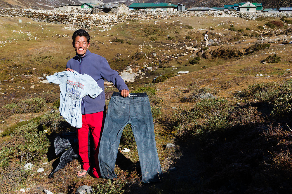Trekking guide showing frozen laundry in Pheriche, Nepal. Photo © robertvansluis.com