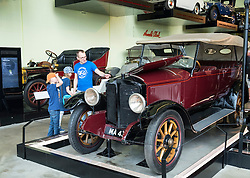 Visitors looking at vintage car on display at Riverside Museum of transport in Glasgow, Scotland, United Kingdom
