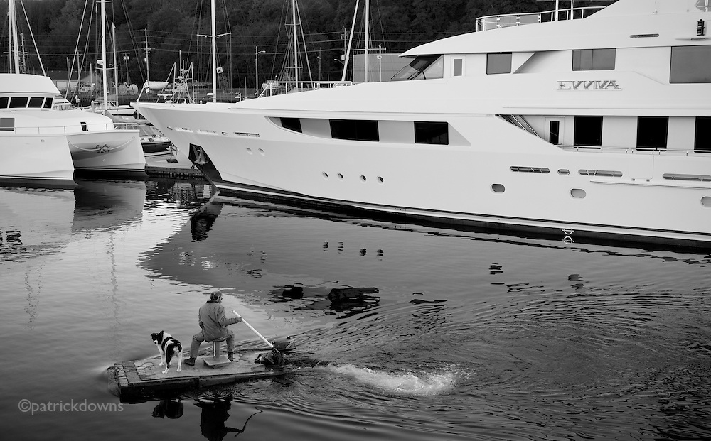 Tale of Two Boats:  A harbor worker and his dog, on little more than a plank with a motor, pass the Evviva, a 150 foot, $40 million dollar yacht. Port Angeles WA