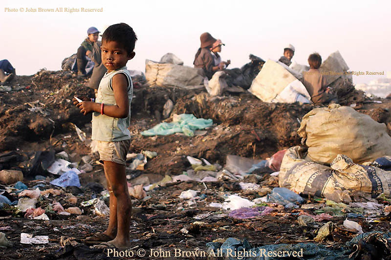 A young worker at The Stung Meanchey Landfill searches for recyclable material without footwear. He is one of the 600 children who work at the dump, some barefooted, located in Phnom Penh, Cambodia.