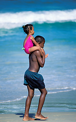 A young black boy carries his little sister on his shoulders along a beach in Trinidad.