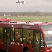 Vliegtuig landend op Schiphol, bus in voorgrond, .openbaar vervoer,