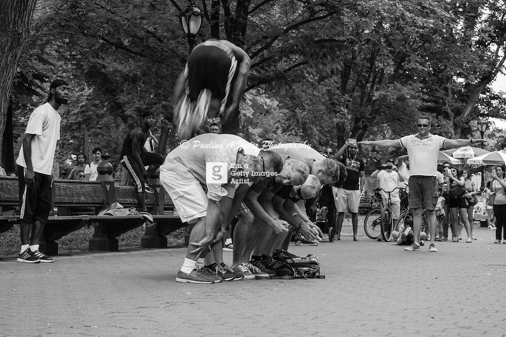 Street Performers 2 Steps Away perform in Central Park. Performer jumps over a group of adult male volunteers.