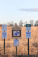Ducks fly over signage at a Waterfowl Production Area and Wildlife Refuge in Wisconsin