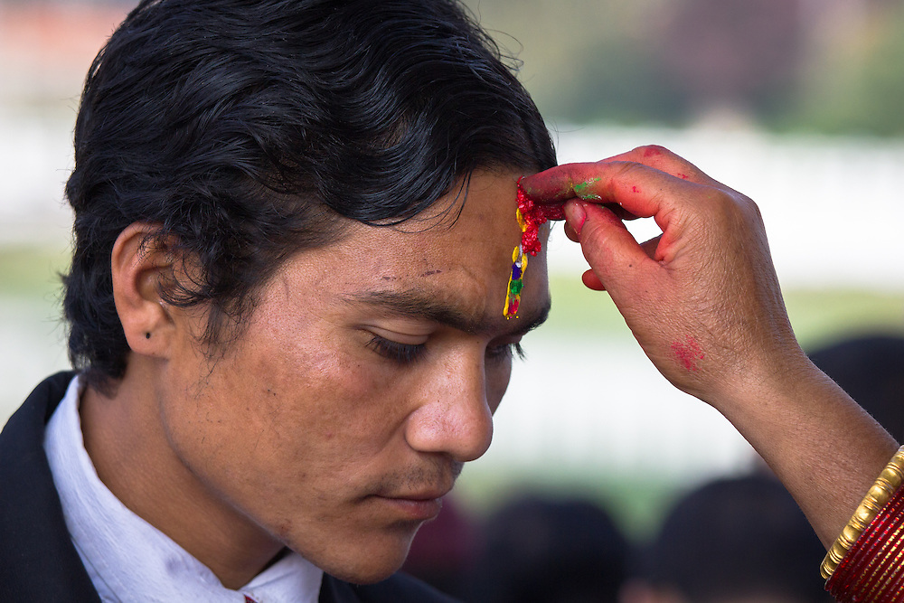 Kathmandu, Nepal. Man receiving his tika. Shot on the fifth day of Tihar, Bhai Tika, on which sisters apply a special tika consisting of five colours (red, green, blue, yellow and white) on the forehead of their brother. Those without a sister, like this particular man, come to the temple to receive the tika.