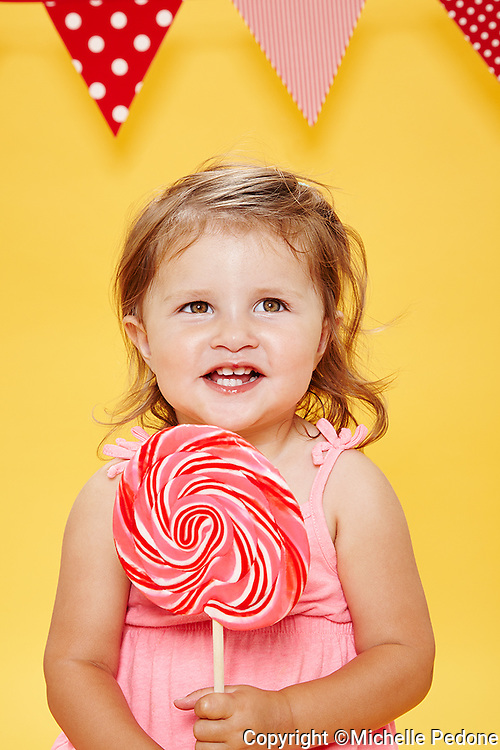 Little girl holding a large red and white swirly lollipop against yellow seamless.<br /> Photographed at Photoville Photo Booth September 20, 2015
