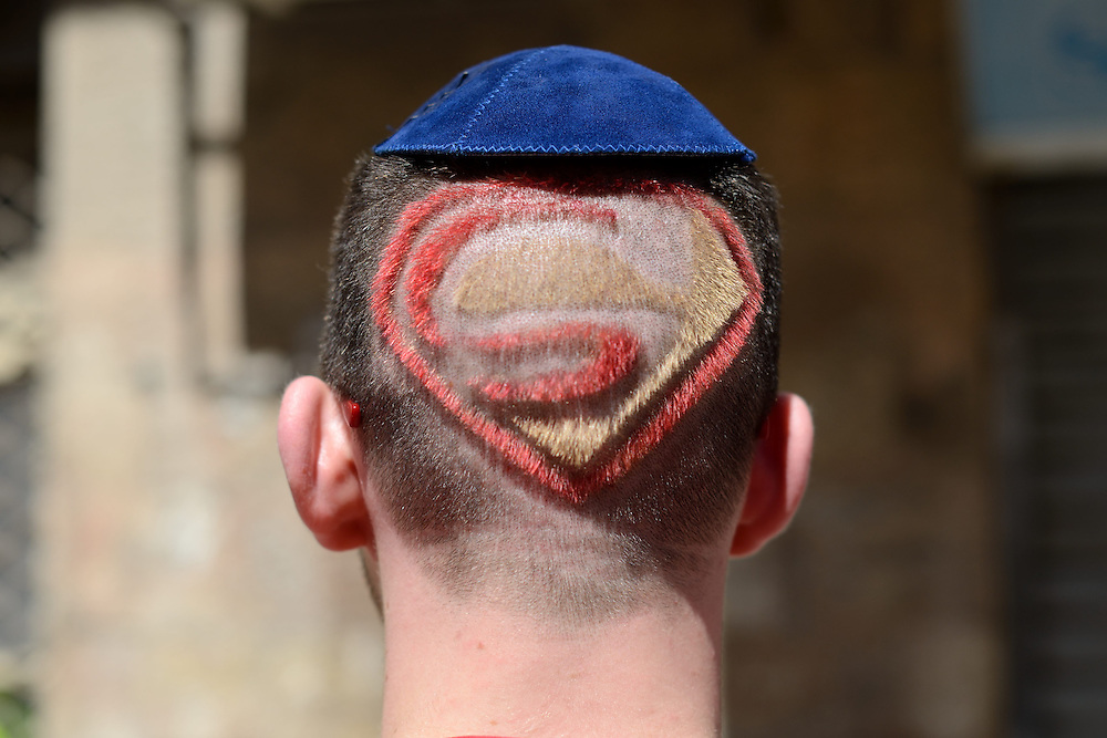 A Jewish man wearing a Kipa and and having a haircut with Superman sign is seen from the back during Purim Holiday in the Ultra-Orthodox Jewish neighbourhood of Mea Shearim in Jerusalem, on March 6, 2015. The Jewish holiday of Purim commemorates the salvation of the Jews living with in the borders of the ancient Persian Empire. Purim customs include food gifts, charity, wearing costumes and drinking heavily.