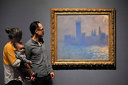 "© Licensed to London News Pictures. 30/10/2017. London, UK.  Visitors view ""Houses of Parliament, Sunlight Effect"", 1903, by Claude Monet at a preview of ""Impressionists in London, French Artists in Exile (1870-1904)"" at Tate Britain.  The exhibition brings together over 100 works by Monet, Tissot, Pissarro and others in the first scale show of French artists who sought refuge in Britain during the Franco-Prussian War and shows views of London as seen through French eyes.  The exhibition runs 2 November 2017 to 29 April 2018.  Photo credit: Stephen Chung/LNP"