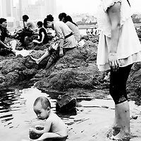 QINGDAO, AUG.23-2010 : a toddler bathes in a puddle by the while his mother stands behind  in Qingdao. Qingdao is one of China's  most renowned beach resorts  and  draws millions of visitors every year which is little by Chinese standards .