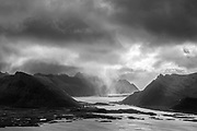 Storm clouds gather and drop rain over the water in Gimsoya, Lofoten, Norway.
