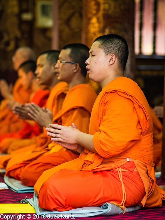 """12 MARCH 2016 - LUANG PRABANG, LAOS: Buddhist monks at a meditation and chanting service at their temple in Luang Prabang. Luang Prabang was named a UNESCO World Heritage Site in 1995. The move saved the city's colonial architecture but the explosion of mass tourism has taken a toll on the city's soul. According to one recent study, a small plot of land that sold for $8,000 three years ago now goes for $120,000. Many longtime residents are selling their homes and moving to small developments around the city. The old homes are then converted to guesthouses, restaurants and spas. The city is famous for the morning """"tak bat,"""" or monks' morning alms rounds. Every morning hundreds of Buddhist monks come out before dawn and walk in a silent procession through the city accepting alms from residents. Now, most of the people presenting alms to the monks are tourists, since so many Lao people have moved outside of the city center. About 50,000 people are thought to live in the Luang Prabang area, the city received more than 530,000 tourists in 2014.       PHOTO BY JACK KURTZ"""