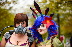 © Licensed to London News Pictures. 25/10/2019. LONDON, UK. Women dressed as (L to R) Krieg from the game Borderlands and Neeko from the game League of Legends join other cosplayers from all over the world attending the opening day of the bi-annual MCM Comic Con event at the Excel Centre in Docklands.  The event celebrates popular culture such as video, games, manga and anime providing many attendees with the opportunity to dress up as their favourite characters.  Photo credit: Stephen Chung/LNP