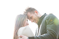 Smiling young man and woman embracing against clear sky
