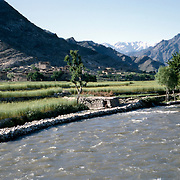 Late Summer? 1965<br /> River in foreground. Mill on jui in center right. Wheat fields ready for harvesting. Ningalam in background. <br /> Snow-capped peaks up Waigal Valley.