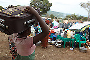 A woman carries a suitcase she purchased at a non-food item fair in the Miketo IDP settlement, Katanga province, Democratic Republic of Congo on Sunday February 19, 2012. Displaced people who have lost most of their belongings as they fleed their homes receive coupons their can exchange for goods at a fair held in partnership with local traders.