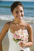 Bride with bouquet on beach smiling (portrait)