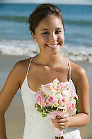 Bride with bouquet on beach smiling (portrait)