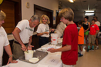 Stan and Sandy Brallier serve ice cream sundaes to volunteer Steven Poloquin with thanks at the completion of the 10 week Got Lunch Laconia program on Monday afternoon. (Karen Bobotas/for the Laconia Daily Sun)