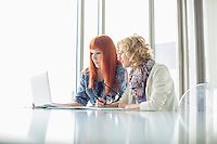 Creative businesswomen working on laptop together in office