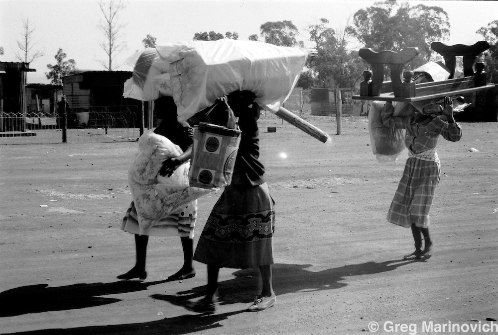 Residents flee the fighting in Phola Park amd the neighbouring hostel in Tokoza Oct 1990, on the East Rand some 20km East of Johannesburg. The migrant workers' hostel was later destroyed in the clashes between Inkatha Freedom Party supporters and those of the African National Congress. (Photo by Greg Marinovich)