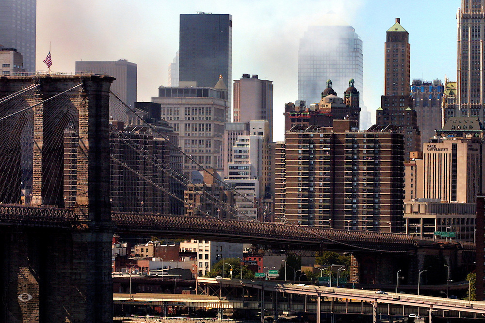 Smoke billows over Manhattan and past the Brooklyn Bridge from the site of the former World Trade Center and surrounding buildings.