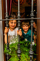 Children looking out onto the street, Calle Ximenez de Enciso, Seville, Andalusia, Spain.