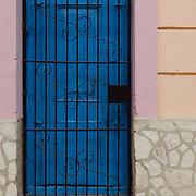 A dark blue door contrasts with the subtle wall colors of Havana, Cuba