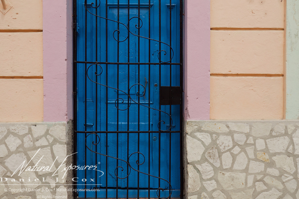 A dark blue door contrasts with the subtle wall colors of Havana, Cuba