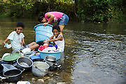A woman and her daughter clean dishes in the river in San Esteban, Honduras on Thursday April 25, 2013.
