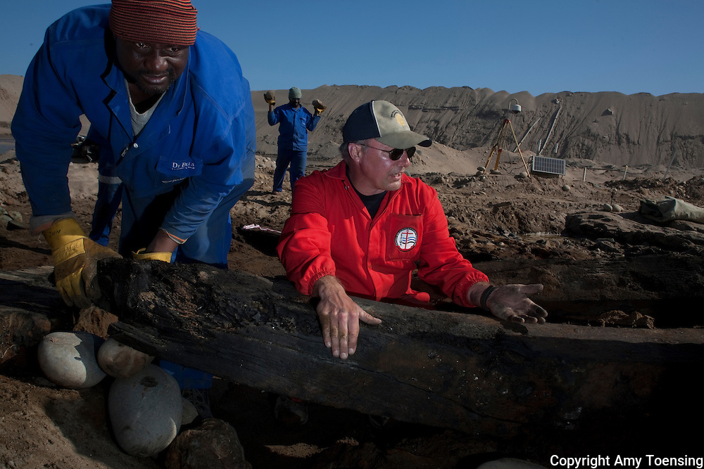 ORANJEMUND, NAMIBIA -- OCTOBER 05: Lead Archeologists, Bruno Werz (Red jumper) and mine workers excavate artifacts on site of shipwreck on October 05, 2008 in Oranjemund, Namibia. The wreck was discovered by miners in the Namdeb diamond mine off the coast of Namibia. The ship was found seven meters below sea level on April 1, 2008. Archeologists presume the wreck is from the early 1500s. Most of the the artifacts found are being stored in a storage shed at the Namdeb Diamond Mine. Items include: copper ingots, bronze canons, canon balls, pewter bowls and plates, ivory tusks from African elephants, and most substantial over 2000 gold coins- approximately 21 kg - the most gold found in Africa since the Valley of the Kings in Egypt. (Photo by Amy Toensing) _________________________________<br />