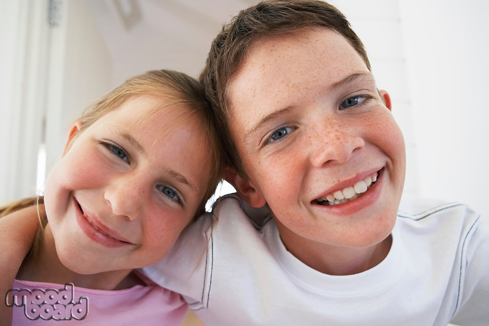 Young boy with arm around young girl portrait close-up