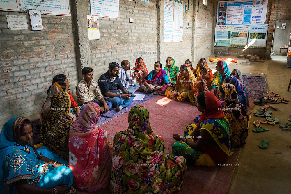 Technoserve's Manager of Market Linkage, Rajiv Shinde, and Jeevika's Field Associate, Jagganath Prasad (on his left), interacts with vegetable farmers during a Producer Group meeting in Machahi village, Muzaffarpur, Bihar, India on October 26th, 2016. Non-profit organisation Technoserve works with women vegetable farmers in Muzaffarpur, providing technical support in forward linkage, streamlining their business models and linking them directly to an international market through Electronic Trading Platforms. Photograph by Suzanne Lee for Technoserve