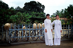 Two girls in traditional Vietnamese dresses, the Ao Dai, near the Caodai Great Temple.
