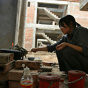 A young labourer cooks lunch at a massive housing project, mimicking a classic American suburb, under construction across the highway from Thang Long Industrial Park, outside Hanoi, Vietnam, Monday, 03 April 2006.